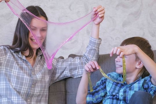Mom and son are playing with slime sitting on the sofa.