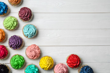 Colorful cupcakes on white wooden background