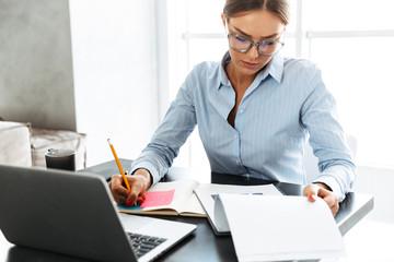 Confident businesswoman working on laptop
