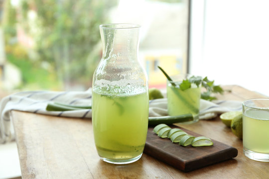 Jug of aloe vera cocktail on wooden table