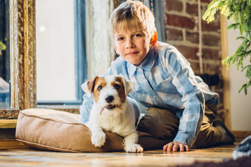 Cute little kid boy with best friend Jack russel terrer dog huugging and looking at camera near the window together. School age boy and dog at home, winter day, cozy lifestyle concept.
