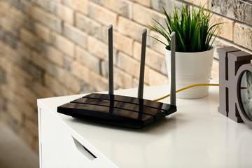 Modern wi-fi router on light commode near brick wall