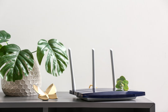 Modern wi-fi router on dark table