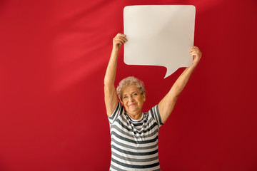 Senior woman with blank speech bubble on color background Wall mural
