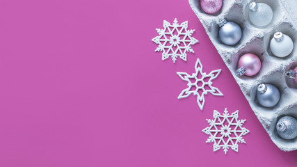 Modern minimalistic Christmas banner background. Pink and silver glitter Christmas tree ornaments in egg packages and shiny snowflakes on pink background mock up. Flat lay, top view