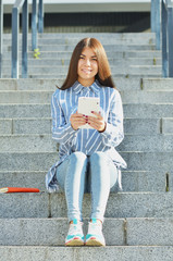A young girl of Asian appearance, a student dressed in jeans and sneakers, holding a tablet and sitting on the stairs