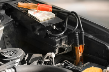 Battery charger under open hood of car