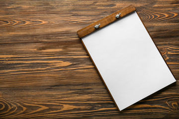 Clipboard with empty sheet of paper on wooden table