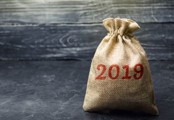 Bag with money and the inscription 2019. Financial budget planning. Investments and plans for the new year. Saving money. Time investment concept. Accumulation