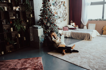 A couple in love passionate embrace to each other lying on the floor in a cozy room with Christmas tree.