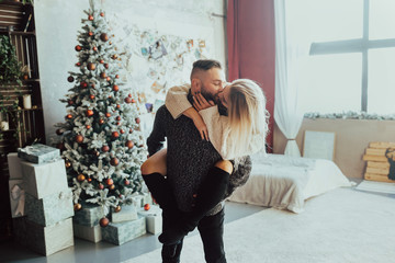 Young romantic couple enjoying spending time together at Christmas in bedroom decorated with beautiful Christmas tree. Happy young guy holding a girl on his back and kissing near the window.