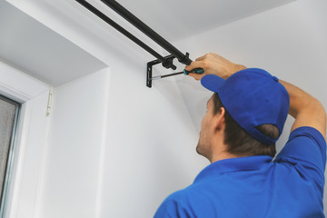 handyman services - worker installing window curtain rod on the wall Wall mural