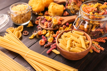 Different types of raw pasta on wooden table