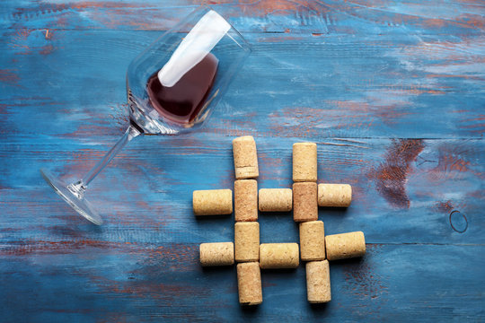 Hashtag sign made of wine corks on color wooden background