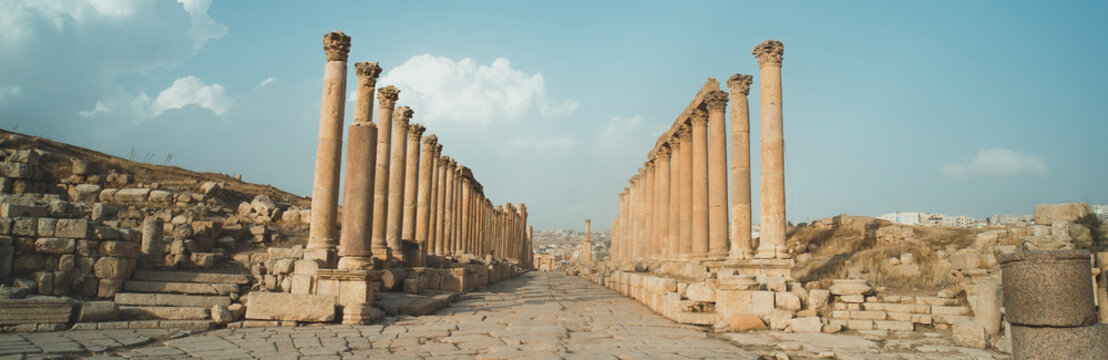 A view looking down the Cardo showing stone carved columns and paved street at the ancient city of Jarash or Gerasa, Jerash in Jordan. ancient Roman sights. Panorama.