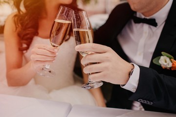 Cropped image of bride and groom clink glasses of champagne during their wedding day, dressed in white dress and black suit, celebrate creating family. Celebration, festive event concept. Newlyweds