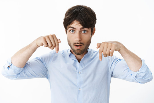 You better look where I point. Persuasive intense and serious good-looking hispanic male with beard and blue eyes raising hands near shoulder as pointing down looking excited over grey wall