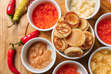Set of tasty caviar with flapjacks on wooden table