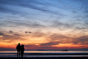 The Silhouette Of Lovers Watching The After Sunset