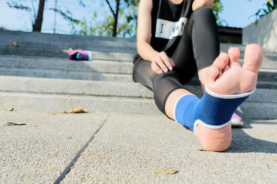 Hand female using elastic bandage with legs,Female putting bandage on her injured foot from sport.