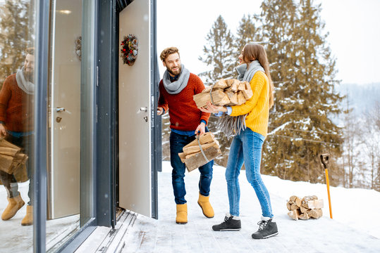 Young lovely couple dressed in colorful sweaters entering their modern home with firewoods in the mountains during the winter