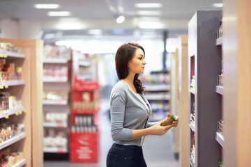 Woman choosing product in supermarket. Reading product information