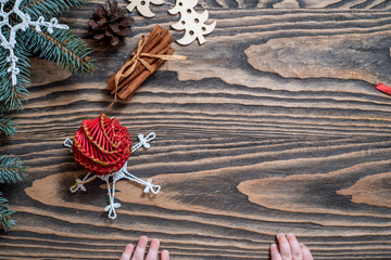 Woman's hands wrap christmas holiday handmade present in craft paper with red tree, fir branch and toy. Christmas gift on wooden rustic table background. Flat lay, top view