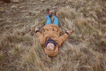 Kid lying on dry grass near creek