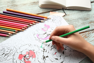 Woman coloring anti-stress picture at table
