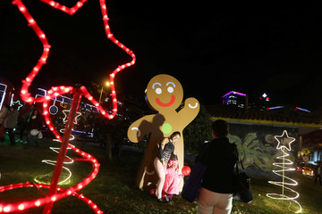 A family poses for a photo next to the Gingerbread Man in Bogota