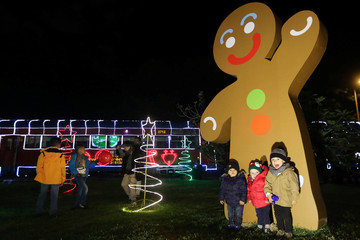 Children pose for a photo next to the tourist train 'La Sabana' decorated with Christmas lights in Bogota