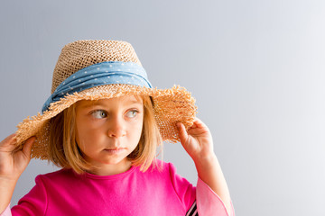 Young pretty girl in straw hat looking away