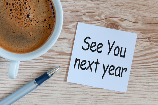 See you next year - memo at wooden office table. 2018 new year coming