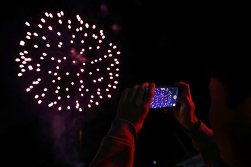 A man takes photos of the fireworks in Bogota
