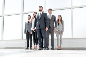 businessman and his business team standing in a spacious office