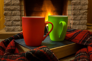 Cozy scene before fireplace with red and green mugs with tea, a book, wool scarf.