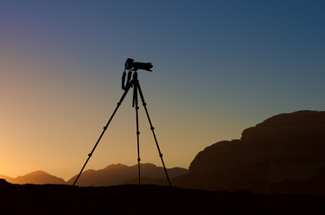 Camera on a tripod isolated in sunrise background. silhouette of camera on tripod with mountains background in sunrise, camera prepared to take photos, tripod. shooting mountains in sunrise or sunset