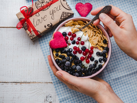 Festive and Healthy breakfast for loved ones. Cereal biscuits in pink glaze, cornflakes, yogurt, fresh berries on the background of white boards. Close-up, top view. Concept of healthy, delicious food