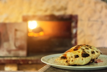 Calzone pizza cooked in the oven on fire Wall mural