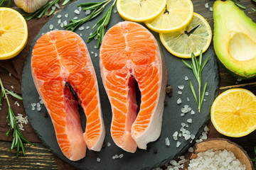 Raw salmon fillets and ingredients, vegetables for cooking on a dark background in a rustic style. Top view, flat-lay, healthy food and clean.
