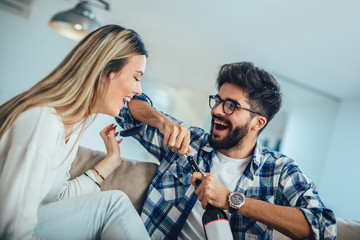 Young couple enjoying wine at home.