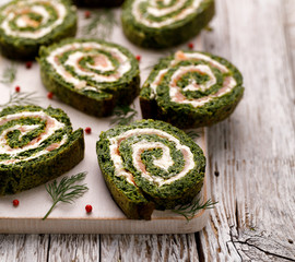 Papiers peints Entree Spinach roulade stuffed with cream cheese and smoked salmon sliced on a white board. Delicious appetizer, party food