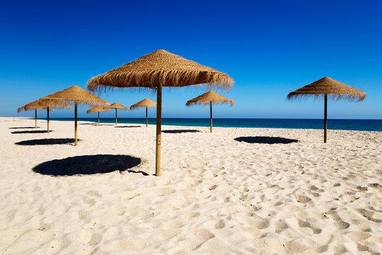 Straw umbrellas on empty white sand beach with clear sea behind, Ilha do Farol, Culatra barrier island, Olhao, Algarve, Portugal