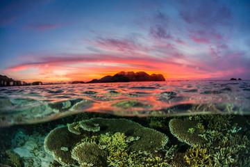 Half above and half below view of the Komodo Diving Resort at sunset, Sebayur Island, Flores Sea, Indonesia