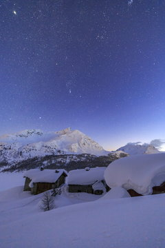 The huts of Spluga covered in thick snow during a clear starry night, Graubunden, Swiss Alps, Switzerland, Europe