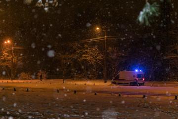 Ambulance on a winter road at night.