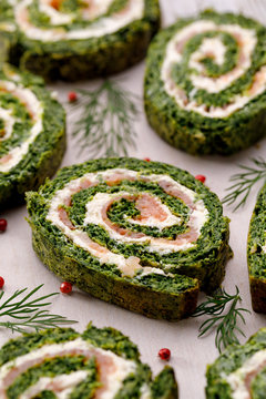 Spinach roulade stuffed with cream cheese and smoked salmon sliced on a white background, close-up.  Delicious appetizer, party food