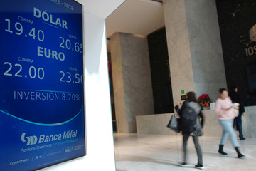 People walk past a board displaying the exchange rates of the Mexican peso against the U.S. dollar and Euro at  a bank in Mexico City