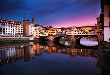 Ponte Vecchio at sunset reflecting in river Arno, Florence