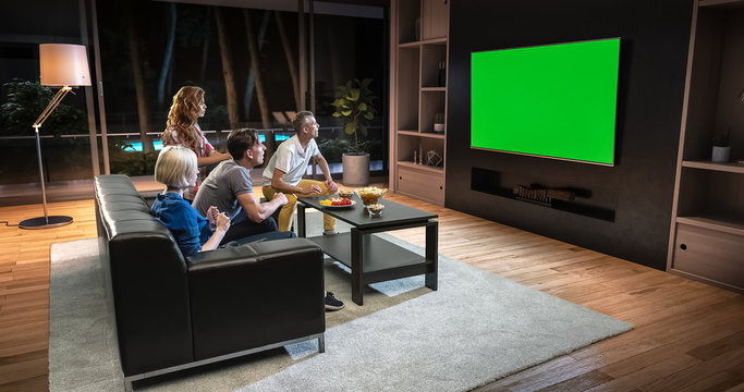 A group of students is watching a TV and celebrating some joyful sports moment, sitting on the couch in the living room.